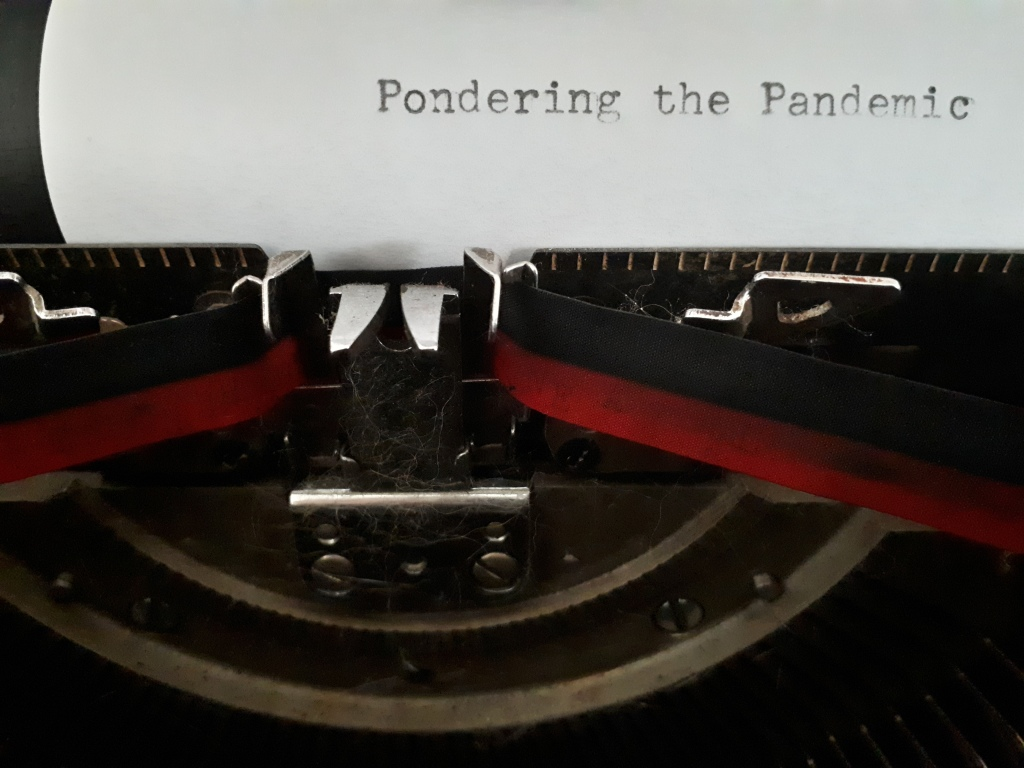 "Photo of typewriter with sheet of paper in it. ""Pondering the Pandemic has been typed on the paper."""