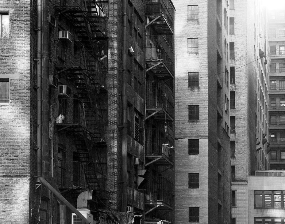 Black and white photo of brick apartment buildings, with metal fire escape platforms and ladders.