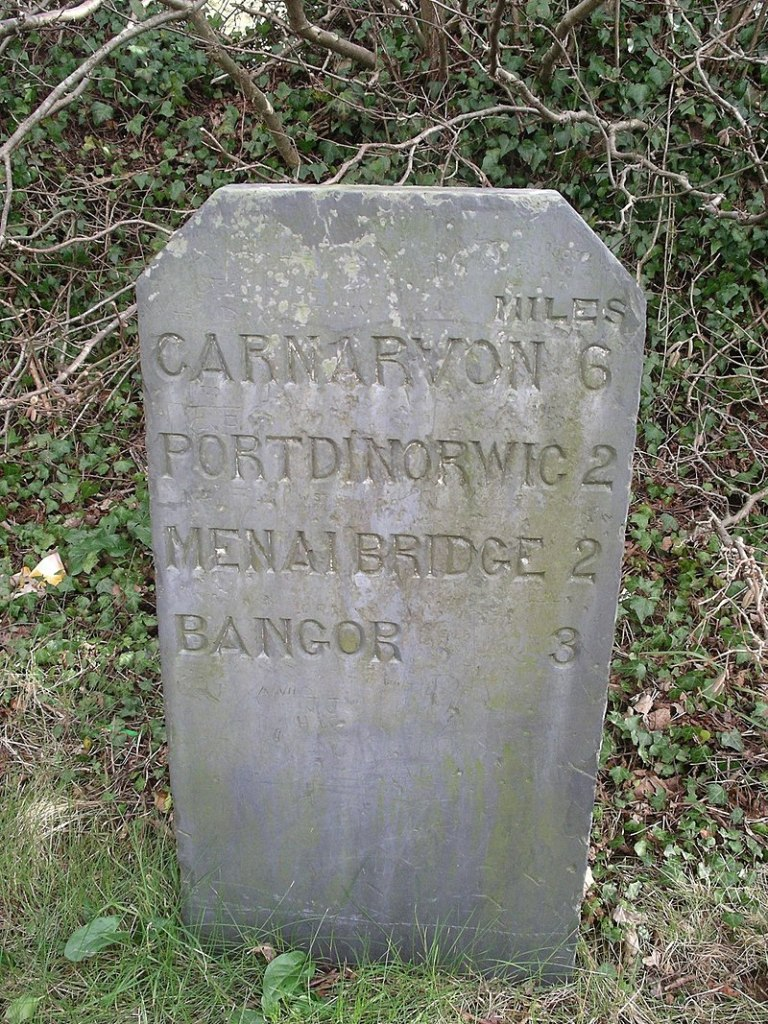 Photo of old milestone in Wales, with distances to various towns. Resembles a headstone for a grave.
