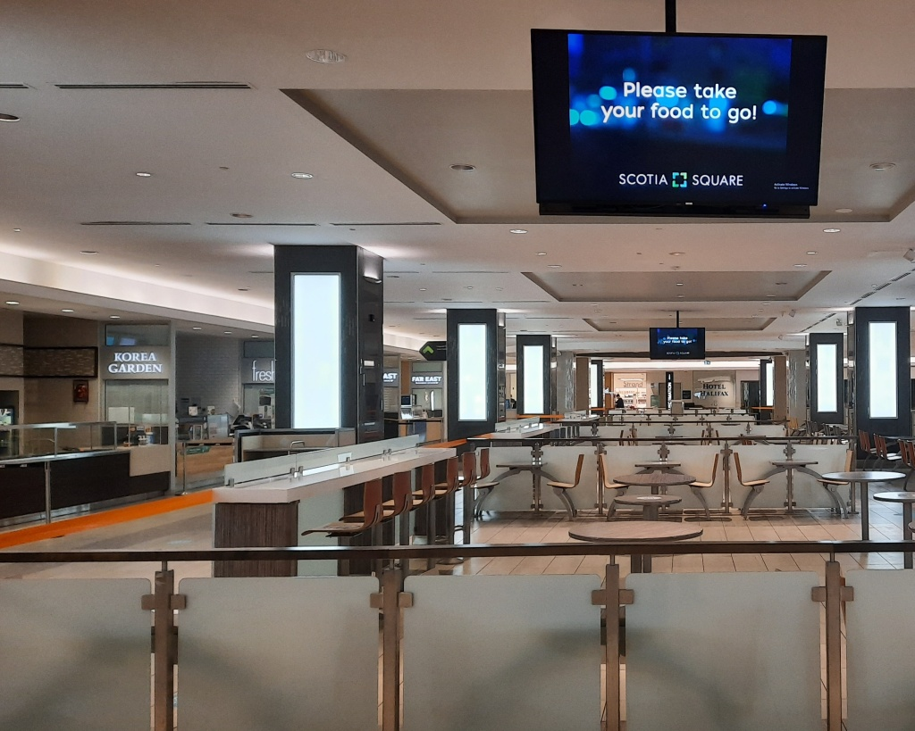 """Food court at Scotia Square mall, showing empty tables in closed seating area, and overhead TV screen stating """"Please take your food to go."""""""