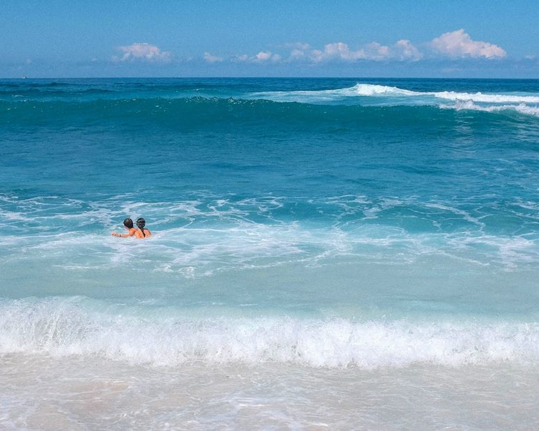 Distant view of two adults standing to their necks  in ocean water near the shore.